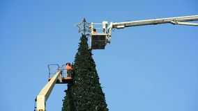 Decoration of a large urban Christmas tree. Workers on the crane install and decorate the Christmas tree stock video