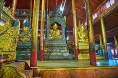 Decoration of Nga Phe Chaung Monastery, Ywama, Myanmar. YWAMA, MYANMAR - FEBRUARY 18, 2018: The row of Buddha images among the wooden pillars in Nga Phe Chaung Stock Image