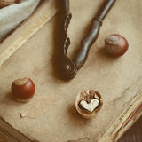 Decoration with nutcracker, heart shaped nut and old books Stock Photo