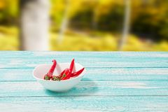 Free Decoration Of Red Hot Chili Pepper On Blue Wodden Board On Blurred Park Background. Set,copy Space,mock Up. Cayenne On White Plate Stock Images - 130548804