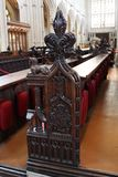 Decoration of pews in Bath Abbey. Decorative elements of pews in Bath Abbey, Somerset, England. Dark carved wood. Aisles and cushions for praying visible Royalty Free Stock Photo