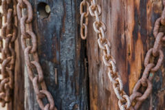 Decoration of pirate chains. A rusty pier portrays the details of a wooden trunk with a decoration of pirate chains Stock Photo