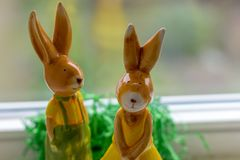Decoration rabbits stands near a window. Two decoration rabbits stands near a window Royalty Free Stock Image