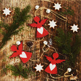 Decoration with red angels with hearts on rustic wooden background Stock Images