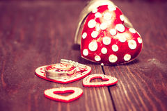 Decoration with red hearts and wedding rings on the wooden backg Royalty Free Stock Images