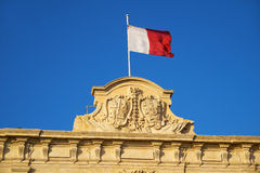 The decoration on the roof of the Auberge de Castille with the c. The decoration topped with a Maltese flag on the roof of the Auberge de Castille now office of Royalty Free Stock Photography