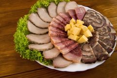 Decoration of sausage, meat, rolls and cheese with lettuce on a wooden background stock photography