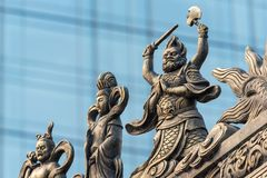 Decoration sculpture on a temple roof. Decoration sculpture on Daci buddhist temple roof against modern building in Chengdu, China stock photo