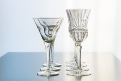 Decoration setup of wine and martini glasses set up in rows on a reflective table top. Wine glasses and martini glasses are set up in rows for a decorative event stock image
