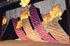 Decoration on stage consisting of Burgundy cloths decorated with yellow leaves stock images