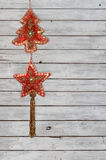 Decoration String with Christmas Tree and Christmas Star Velvet Ornaments on Weathered Wooden Background. Decoration string made of a Christmas tree and a royalty free stock photo