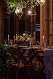 Decoration table before a banquet in a wooden barn. Decoration wedding table before a banquet in a wooden barn. Evening. Burning lights. Candles, bouquet Stock Photo
