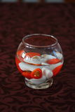 Decoration for the table. Glass with colored stones floating in the water Royalty Free Stock Images