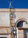The decoration of the unidentified building, represents the climbing men on the step and a woman standing on top royalty free stock photo