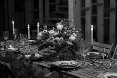 Decoration wedding table before a banquet in a barn. Decoration wedding table before a banquet in a wooden barn. Candles, bouquet, stemware. Black and white Royalty Free Stock Images
