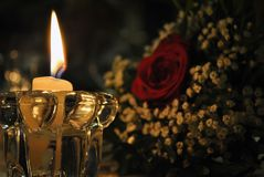 Decoration of a white candle and a bouquet of flowers stock images