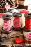 Decoration with wooden spools and red ribbons Stock Images