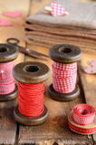 Decoration with wooden spools and red ribbons Royalty Free Stock Images