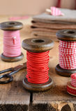 Decoration with wooden spools and red ribbons Royalty Free Stock Image