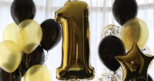 Decoration for 1 years birthday, anniversary. Decoration for birthday, anniversary, celebration of the first anniversary, white background and gold balloons stock footage