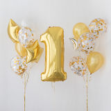 Decoration for 1 years birthday, anniversary. Decoration for birthday, anniversary, celebration of the first anniversary, white background and gold balloons royalty free stock image