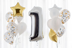 Decoration for 1 years birthday, anniversary. Decoration for birthday, anniversary, celebration of the first anniversary, white background and gold balloons stock photos