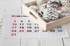 Decorations and calendar with Christmas Day marked out Stock Photo