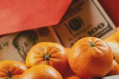 Overhead of top decorations Chinese New Year festive mandarine oranges background concept Chinese Yuan bills vs U.S. dollar. Decorations Chinese New Year festive stock photo