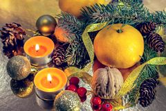Christmas decorations, new year. Christmas Eve. composition. Mandarins. oval branches. cones. candles on a golden shiny background royalty free stock images