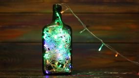 Decorations for the New Year. Garland with flashing lights inside the bottle. Creative solutions. stock video