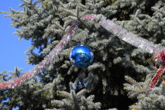 Decorations New Year tree. Tinsel and toys, balls and other decorations on the Christmas Christmas tree standing in the open air Stock Image
