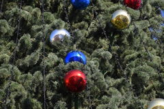 Decorations New Year tree. Tinsel and toys, balls and other decorations on the Christmas Christmas tree standing in the open air Royalty Free Stock Photo
