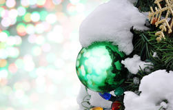 Decorations and snow on a Christmas tree. Glass Christmas ornament hanging on tree with colorful bokeh in background royalty free stock images