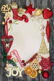 Decorations and Symbols of Christmas. Forming a border with gold joy sign, baubles, holly, mistletoe, fir, mince pie, cinnamon sticks and dried orange on rustic Royalty Free Stock Image