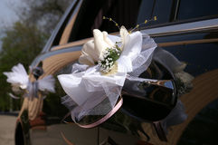 Decorations on the wedding car. Artificial flowers on the door handles black car Stock Images
