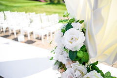 Decorations for the wedding ceremony. Flowers closeup. White flowers with green leaves, white wedding, exit ceremony, wedding in nature, floristry, decor, sunny Royalty Free Stock Photos