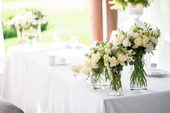 Decorations for the wedding ceremony. Flowers closeup. White flowers with green leaves, white wedding, exit ceremony, wedding in nature, floristry, decor, sunny Stock Photos
