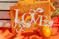 Decorations word love on an orange background in the summer Stock Photos