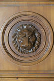 Decorative adornment on a wooden door. Decorative adornment in form of the head of a lion on a brown wooden door Stock Image