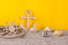 Decorative anchor and steering wheel with seashells in the sand on a yellow background royalty free stock photo