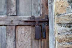 Decorative Antique Door Latch. Detail of a stone building and an old wooden entrance door with antique door handle Stock Image