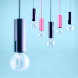 Decorative antique edison style filament light bulb on light blue background. Filtered image Royalty Free Stock Images