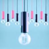 Decorative antique edison style filament light bulb on light blue background. Filtered image Stock Photos