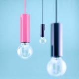 Decorative antique edison style filament light bulb on light blue background. Filtered image Stock Image