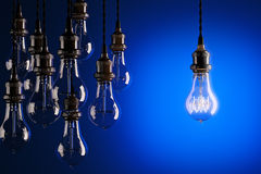 Decorative antique edison style light bulbs against a blue background. Stock Image