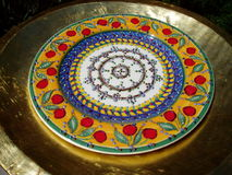 Decorative antique plate. Closeup of decorative antique plate or bowl with bronzed background stock photography