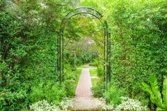 Decorative arched iron gateway to a garden stock photos