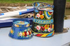 Decorative art work on canal narrowboat. Colourfully decorated bowl and pail on a canal narrowboat in England stock image
