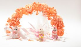 Three cute baby dolls sitting in front of plastic flowers wreath. Decorative artificial flower garland with three cute baby dolls Royalty Free Stock Images