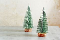 Decorative artificial small Christmas trees on a light background. Christmas composition with copy space. royalty free stock photo